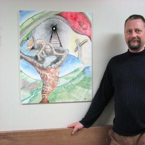 Mike, a member of the Client Advisory Council at the Brockville Mental Health Centre stands by his painting