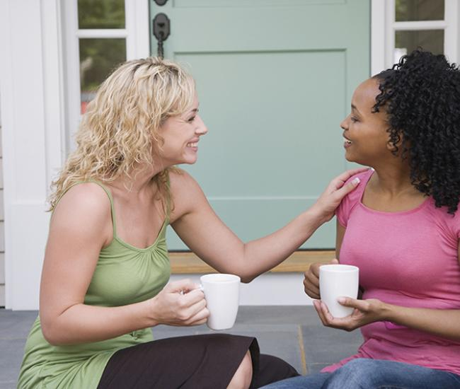 two women talking and holding coffee