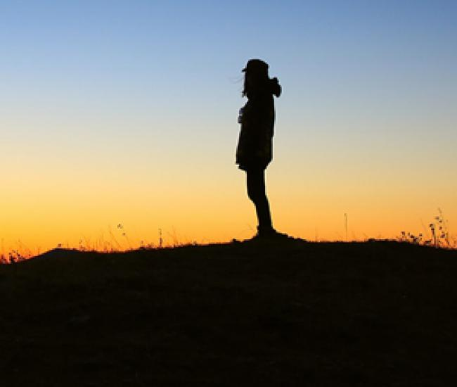 Silhouette of youth standing outside at sunset